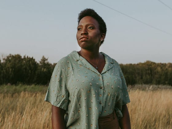 A black woman with short hair standing in a field looking in the distance