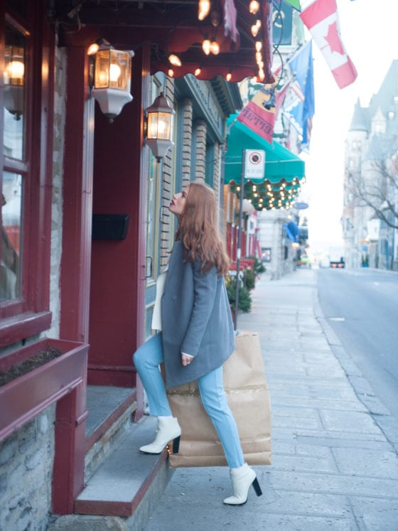 A woman in a jacket and boots walking into a cafe from the road