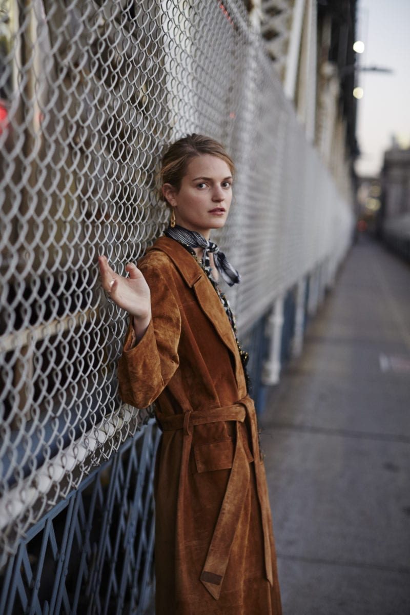 A woman wearing a long suede jacket leaning against a wire gate while looking outward to the camera