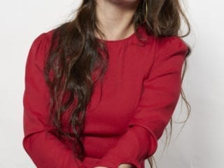 A woman in a red dress and red lipstick smiling as she sits facing the camera against a white background