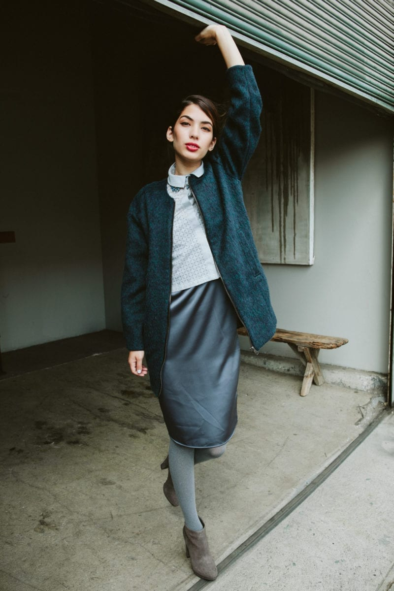A woman in a sweater and skirt holding up a garage door while staring at the camera