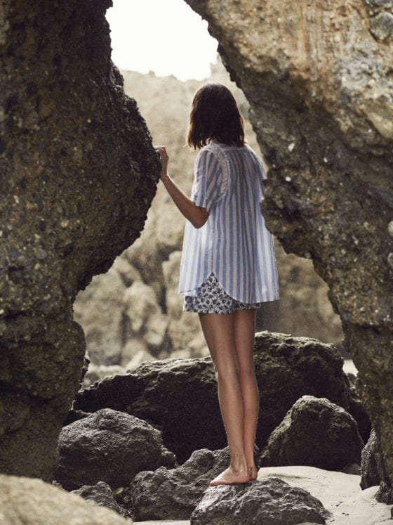 Woman in striped shirt and shorts standing in a alcove of large rocks lookin out in the distance