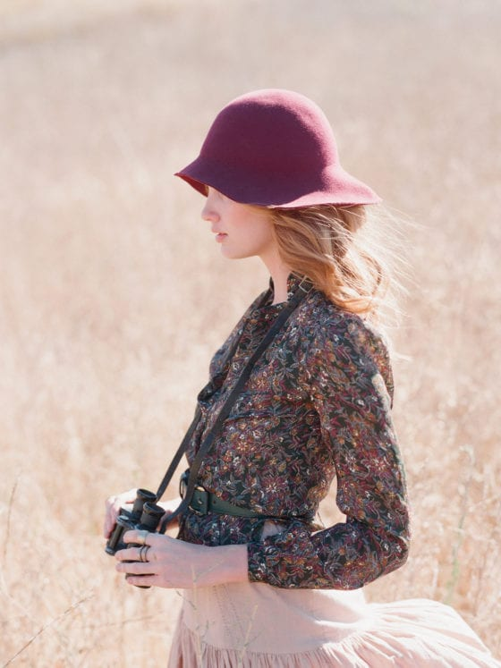 A woman with a hat, long-sleeved top and skirt standing in a field with binoculars
