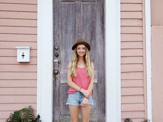 A woman in shorts, a tank top and fedora hat standing in front of the door of a home