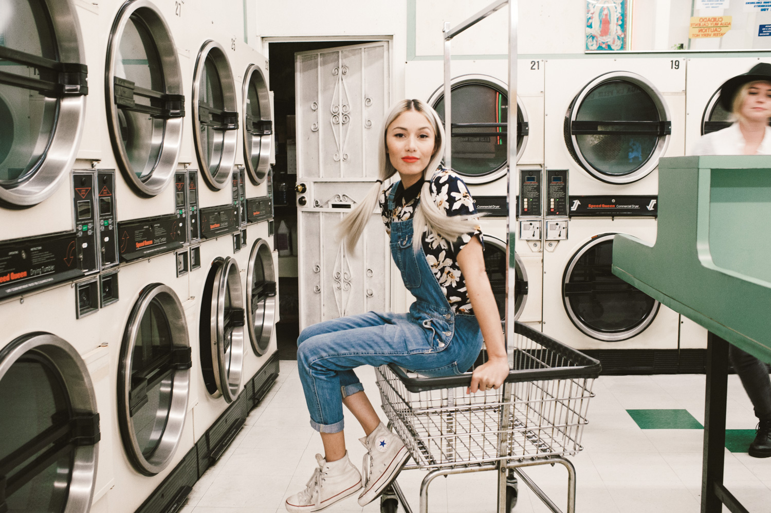 A woman sitting on a cart as she rolled down an aisle at a laundry mat