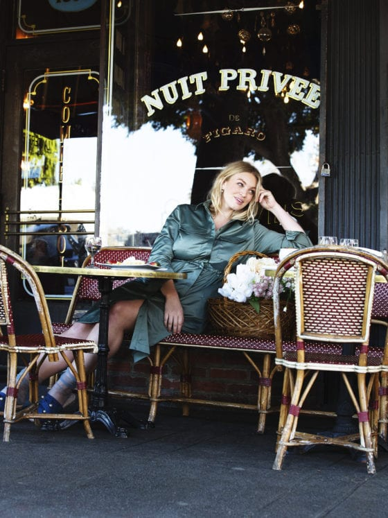 A woman sitting outside of a French cafe