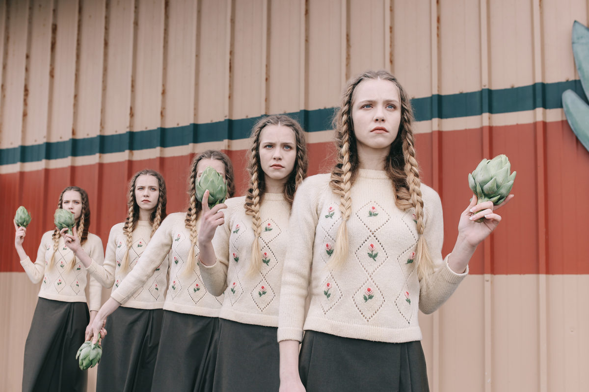 Five identical women dressed in the same outfit holding a vegetable in front of a garage