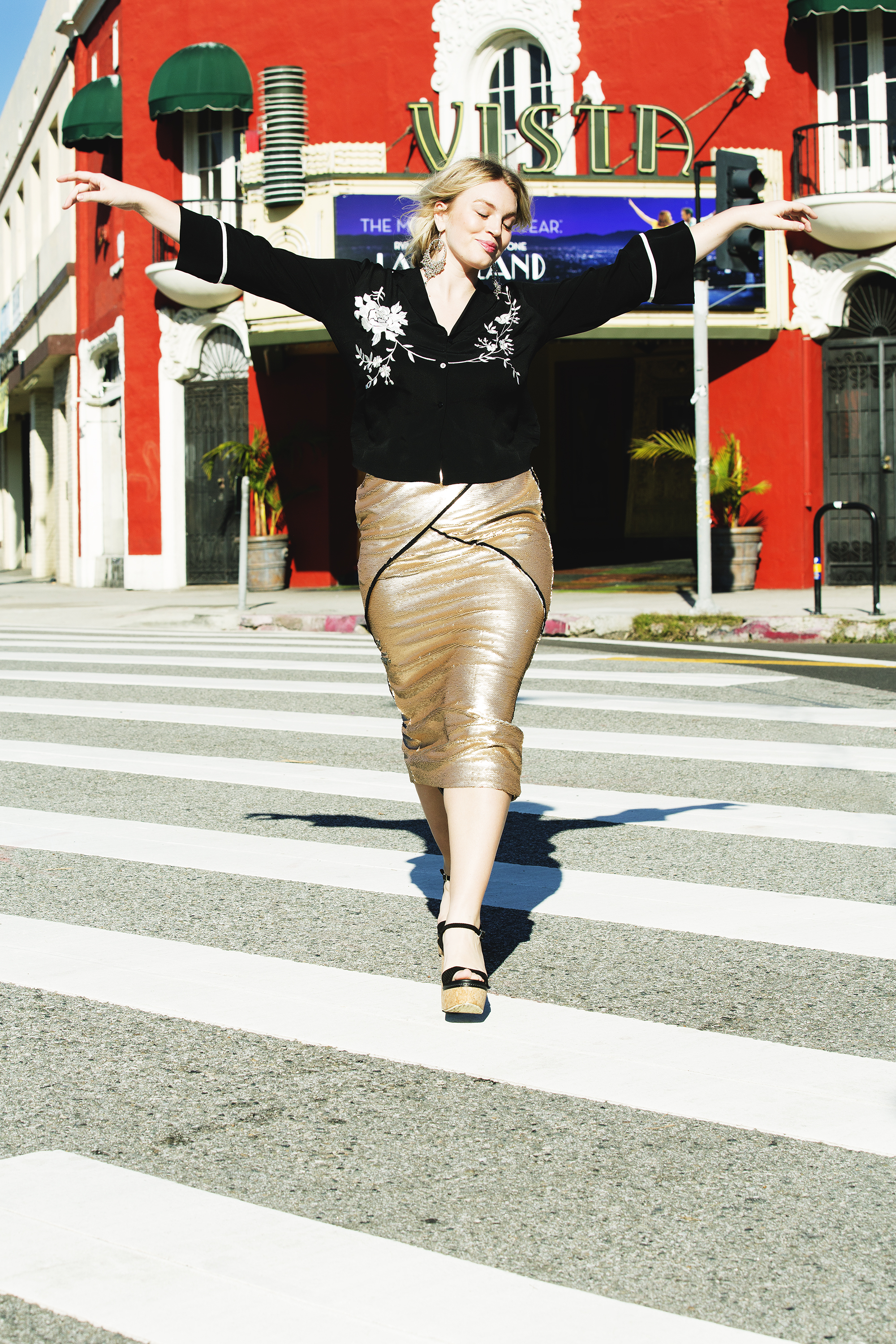 A woman prancing down a city street with her arms outstretched