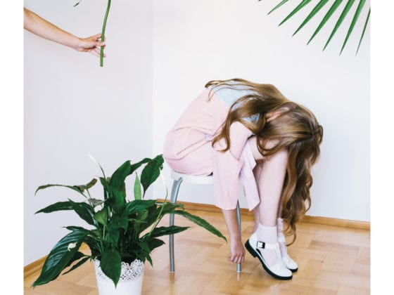 A woman bent over in a chair with her hair falling over her face as a hand holds a plant toward her