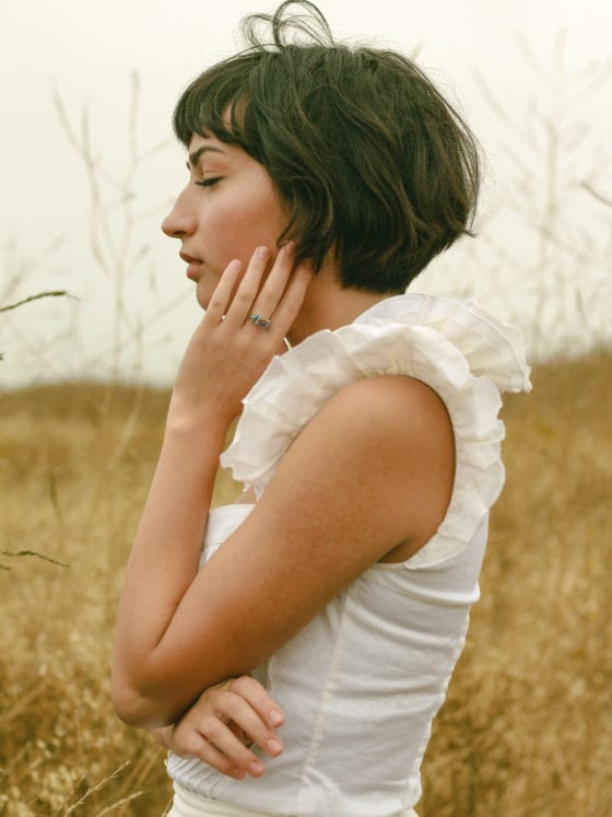 A side profile of a woman standing in a field with her eyes closed and her hand to her face