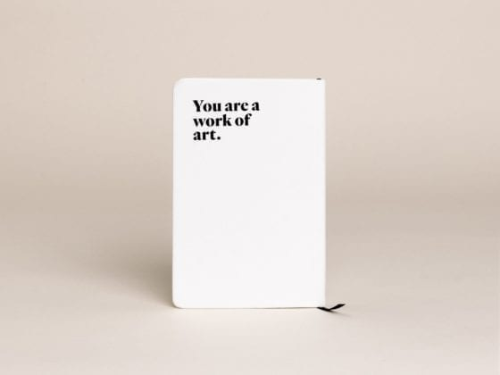 "The back of a Darling journal that says, ""You are a work of art."""