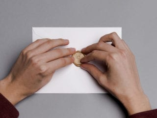 hands touching the seal on an envelope