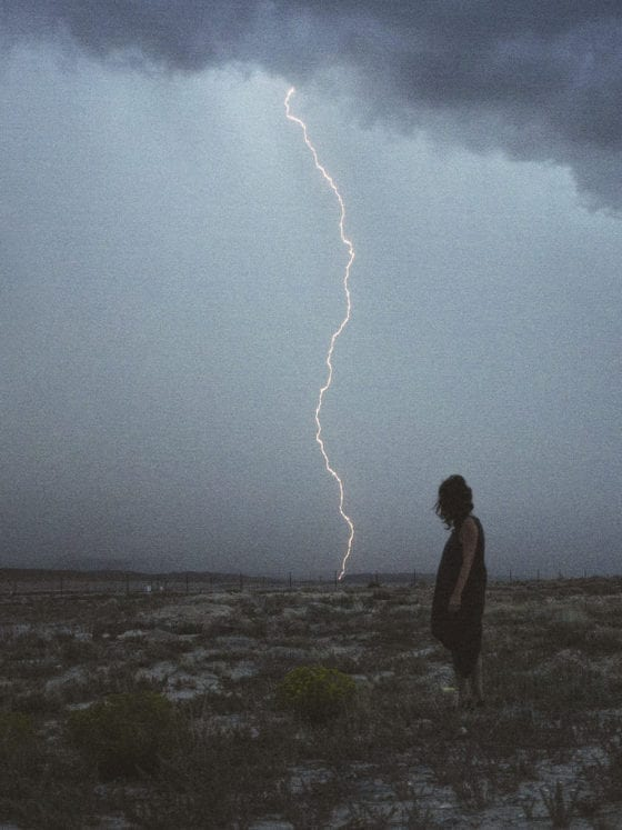 A woman standing in a field with lightning