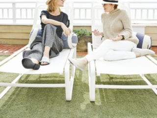 A mom and her daughter looking at each other as they sit on patio chairs