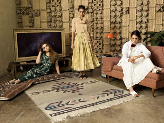 A group of three woman in a small living room, one seated on the couch, another on the floor and one standing