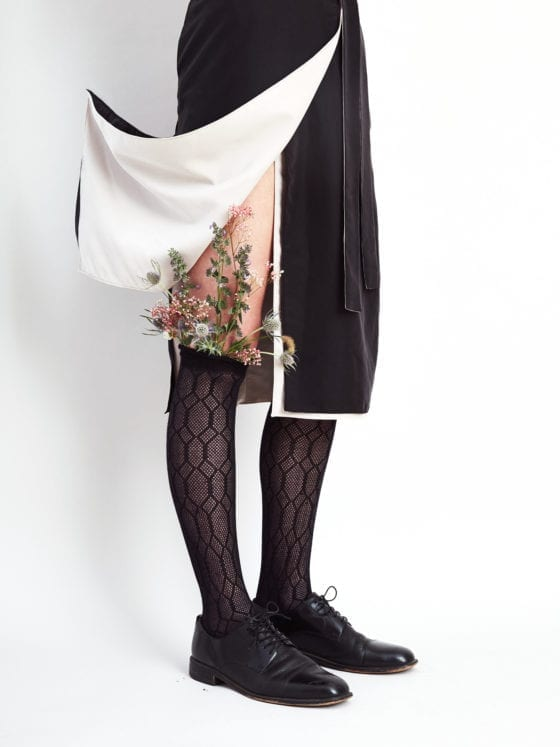 A woman's skirt pulled up to expose her knee high socks that have flowers sprouting out of them