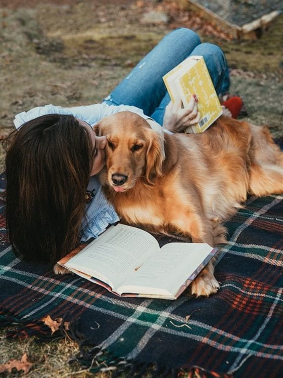 A woman lying on a blanket next to her dog as she reads