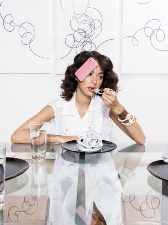 A woman with a phone stuck to her face as she sits at a dinner table with phone cords on her plate