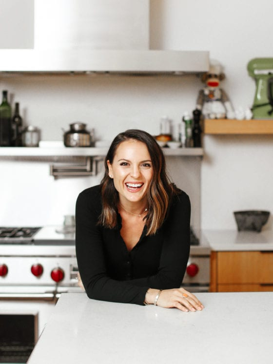 A woman smiling as she leans over a kitchen counter