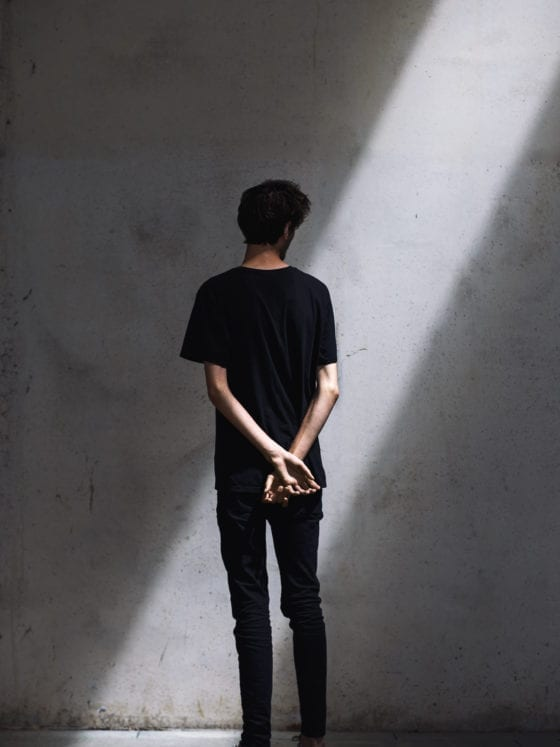 A picture of the back of a man who is facing a wall