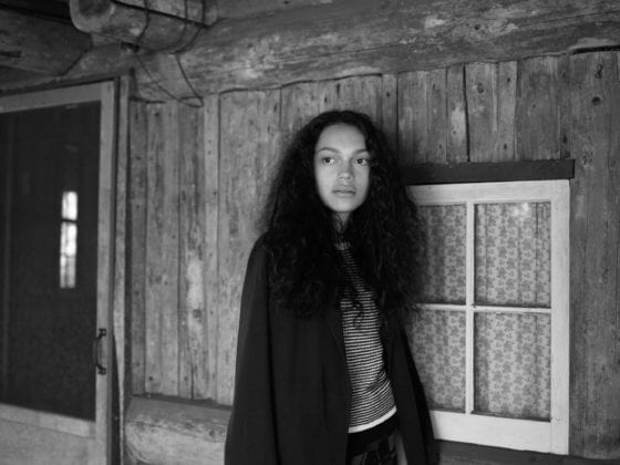 A black-and-white photo of a black woman with long hair and a black jacket standing outside of a cabin