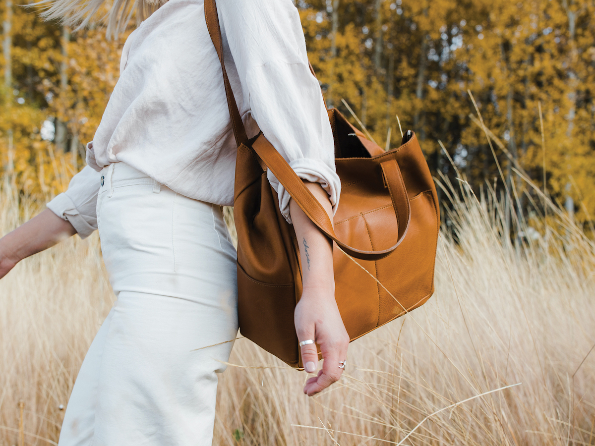 A woman walking through a field with a leather bag