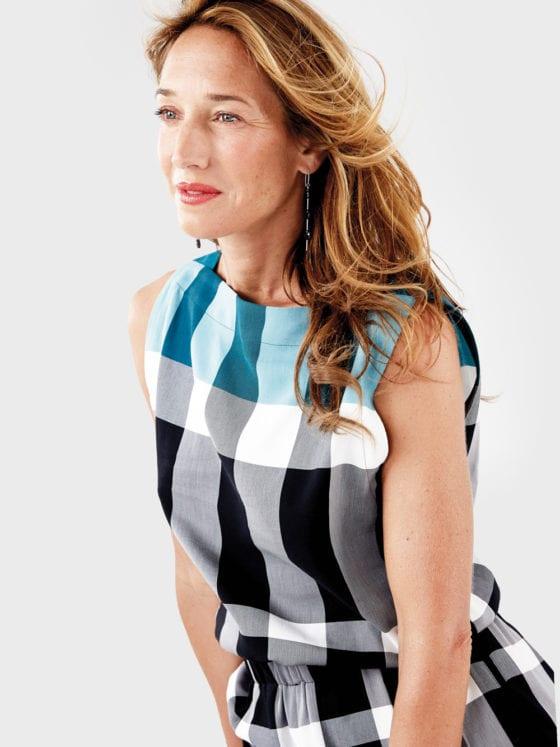 A woman in a plaid dress leaning forward