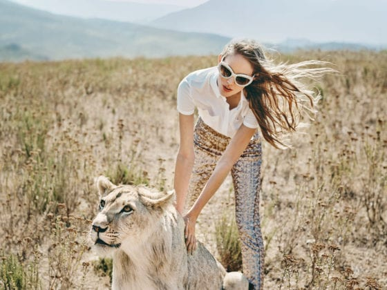 A woman in a grassy plain petting a tiger