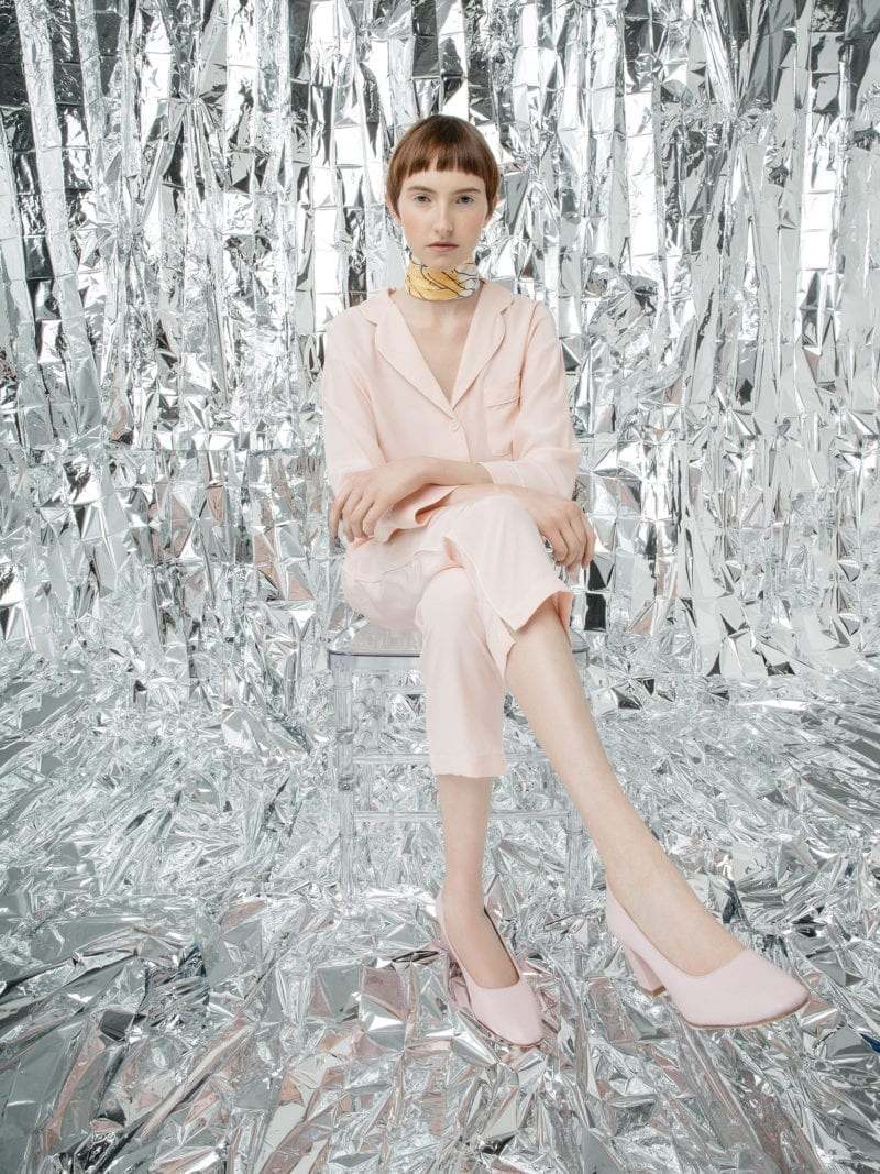 A woman in a pants suit seat in a room covered with aluminum foil material