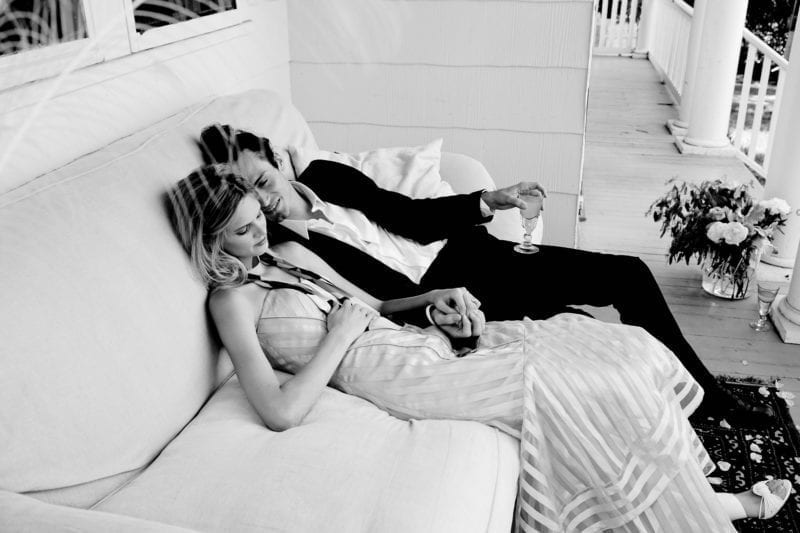 A married couple sitting on a couch on their wedding day