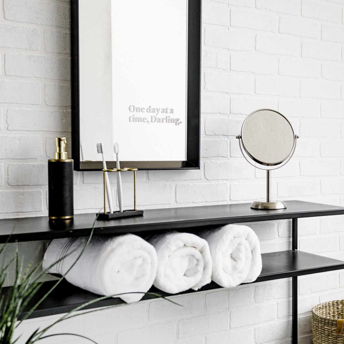 A bathroom dresser with towels, a mirror, hand soap, towels and a mirror on the wall