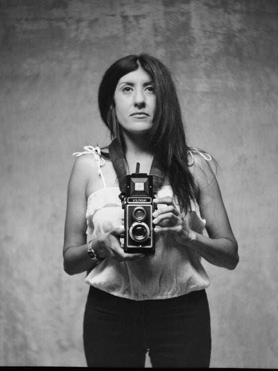 A black and white photo of a woman holding a camera