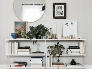 A book stand with greenery on it and a mirror hanging on the wall behind it