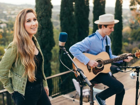 A woman singing with a guy to her left playing the guitar