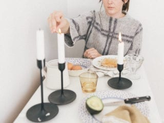 A woman lighting a candle at a dinner table