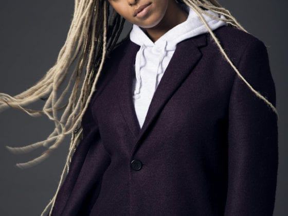 A black woman with long blonde braids blowing in the wind