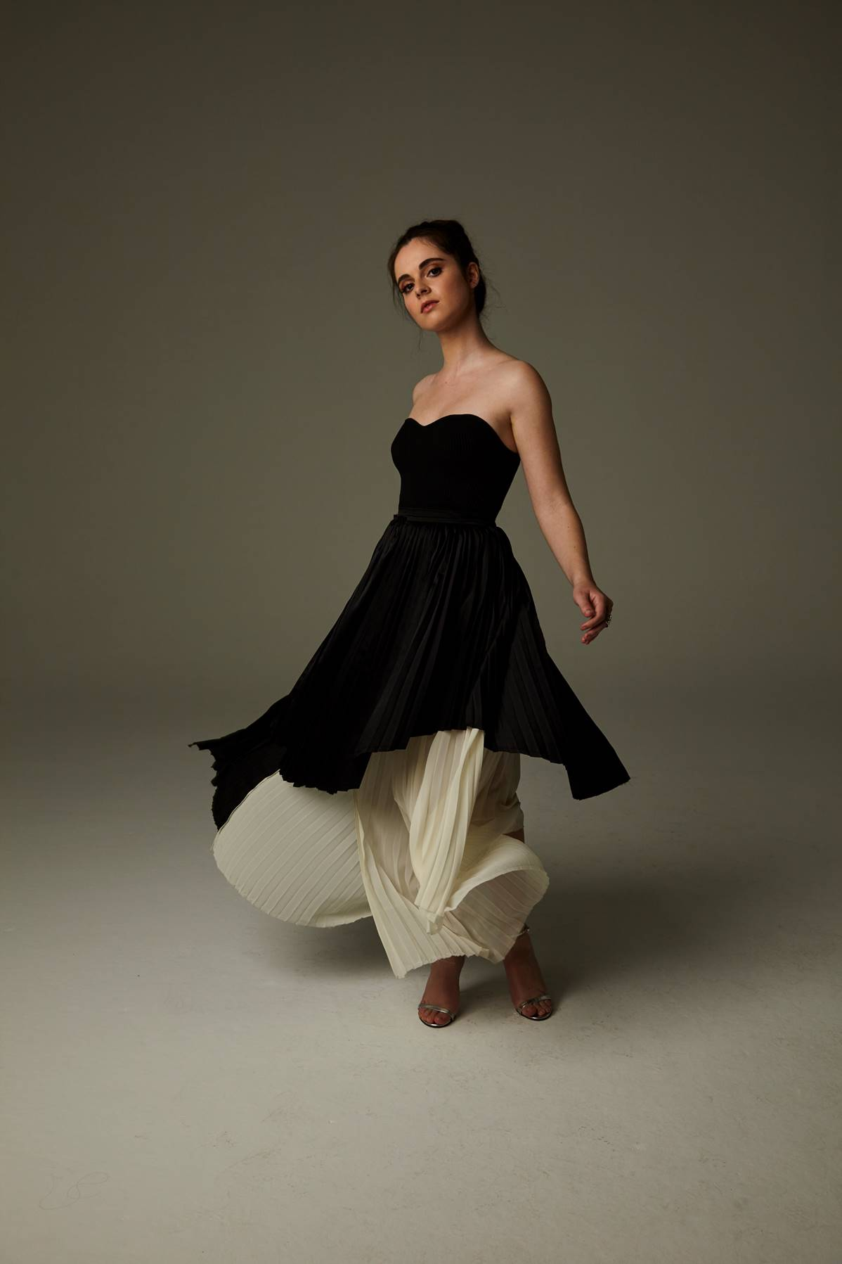 A picture of a girlin a black strapless, flowy dress