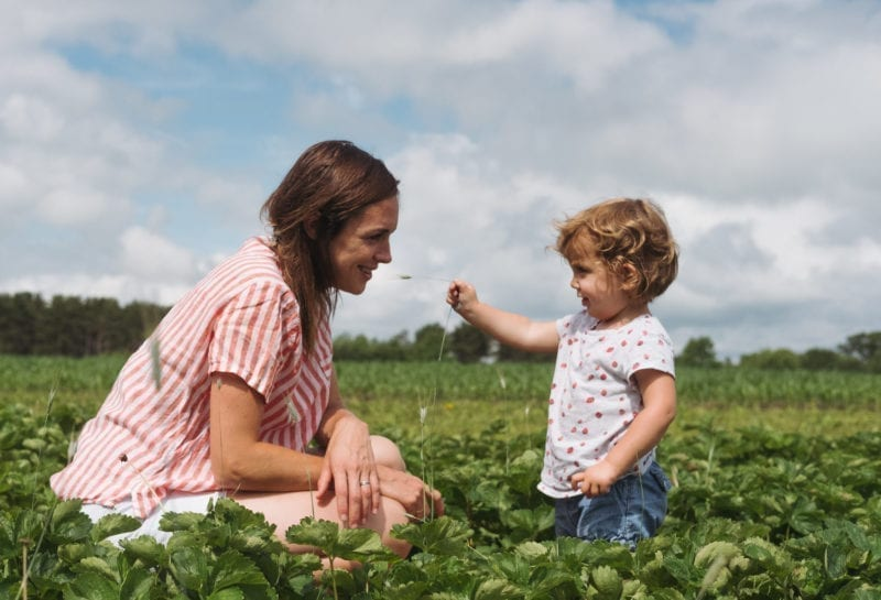 A mom and a daughter standing in a field as the baby girl holds a flower up to her moms face