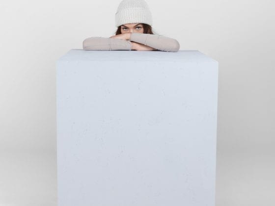 A woman wearing a beanie kneeling behind a cube with her upper torso leaning over the block