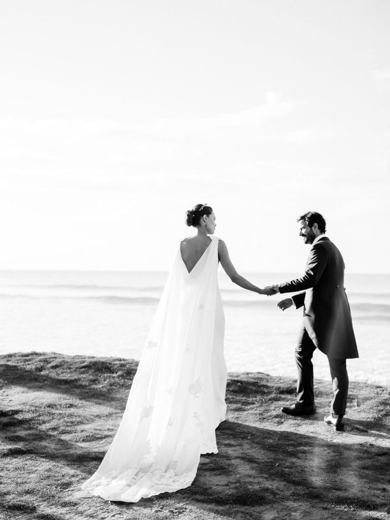 A couple walking along the beach on their wedding day