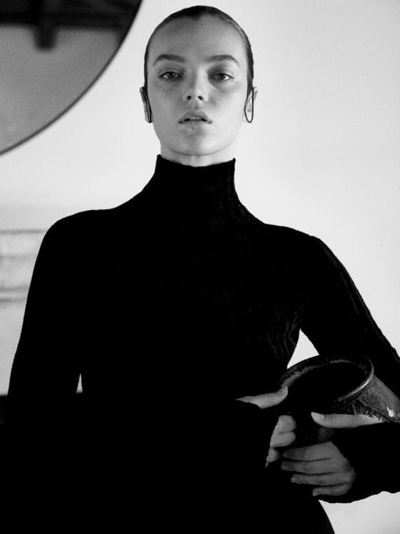 A black and white photo of a woman with her hair slicked back