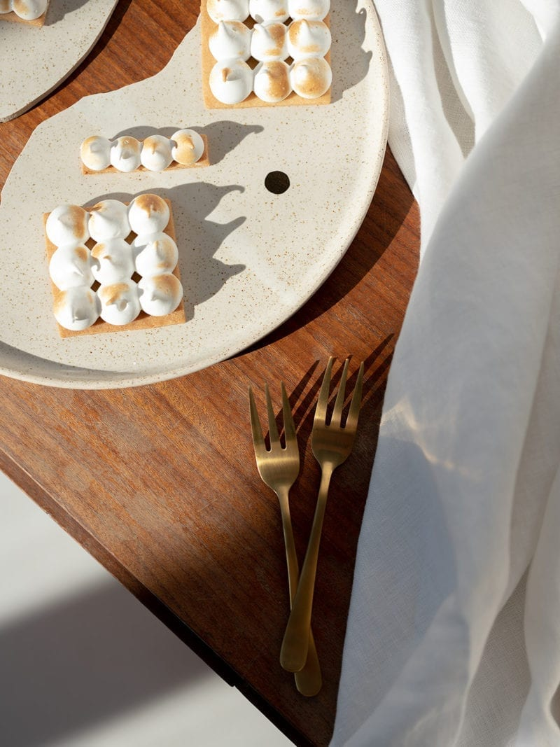 A picture of two forks, a table cloth, and a broken plate of desserts on a table