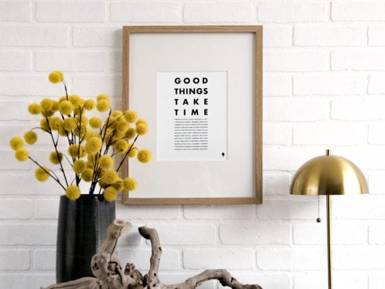 "A piece of art that says ""Good Things Take Time"" near a table with a lamp and flowers"