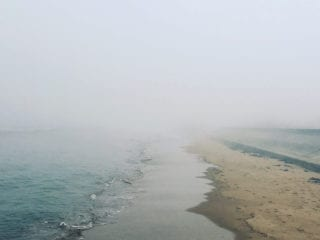 A foggy day at the beach as the waves meet the shore