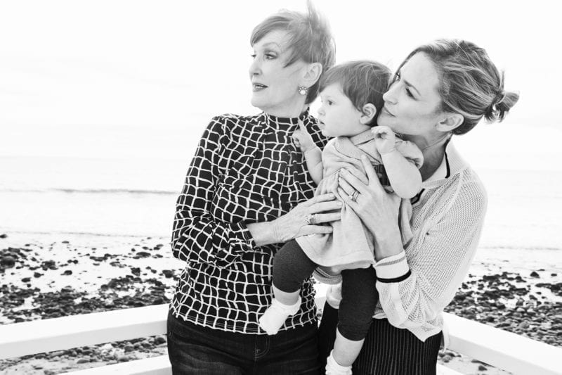 A grandmom, mom and little boy embracing as they look off into the distance