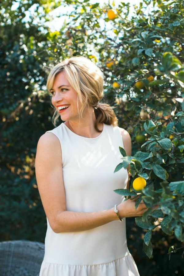 A smiling woman looking over her shoulders as she stands next to a lemon tree