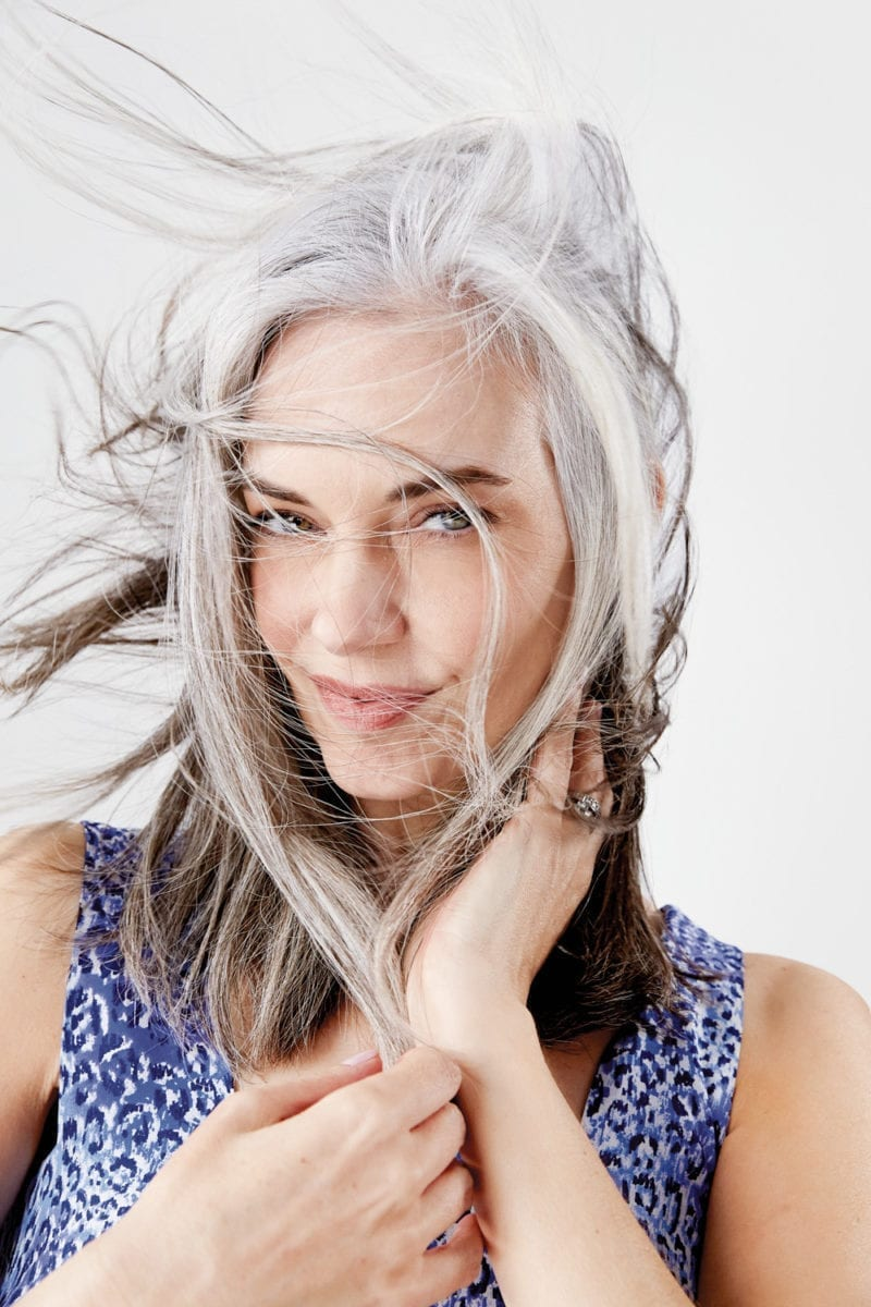 A smiling woman whose gray hair is blowing around her face