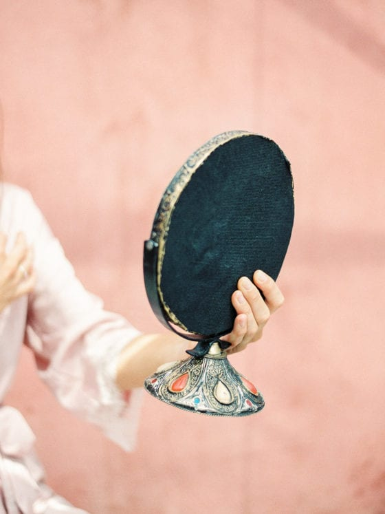 A woman's hand holding a oval-shaped vanity mirror
