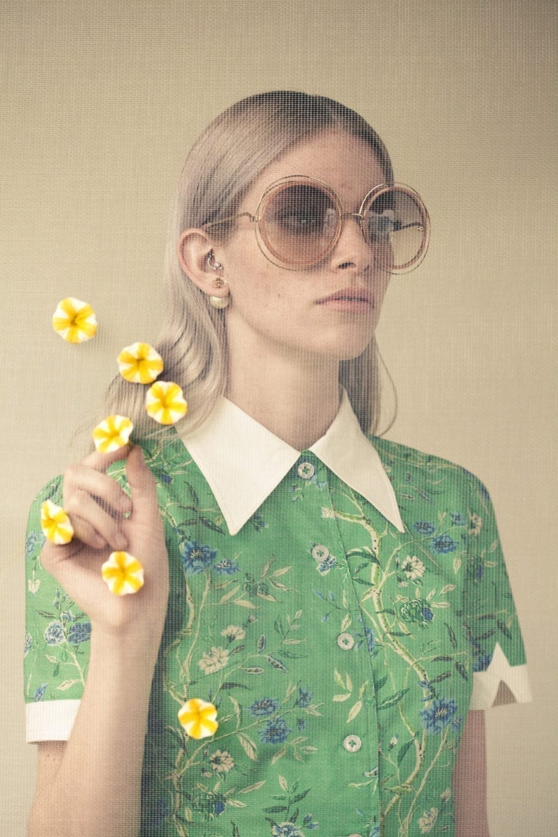 A woman with sunglasses holding flower petals