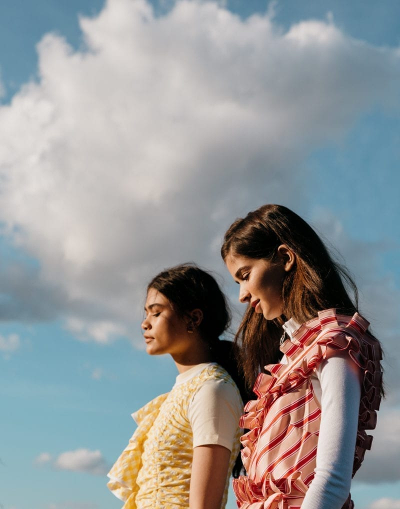 Two women standing side by side outside under the clouds